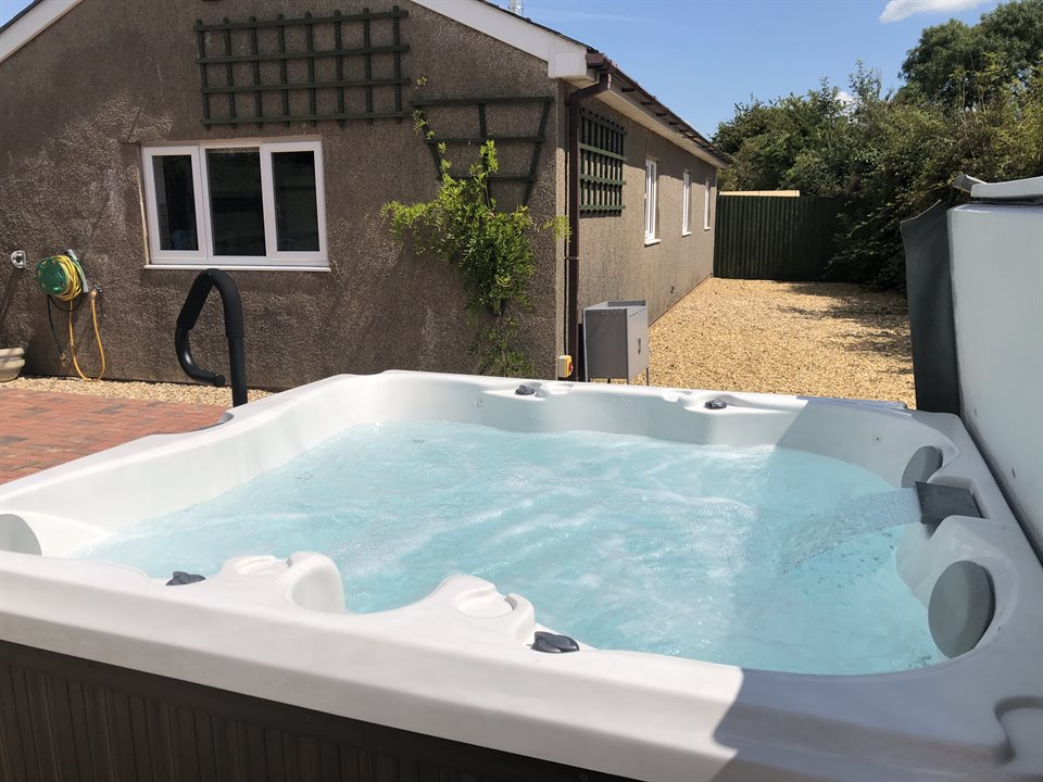 Close up image of the Jacuzzi showing its proximity to Hawthorn Lodge and the private garden area which can also be used to safely store cycles